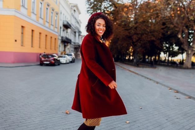 Улыбающаяся девушка в удивительном зимнем наряде и аксессуарах позирует на улице