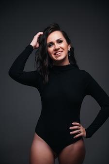 검은 벽에 bodysuit에서 웃는 소녀