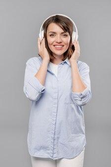 Улыбающаяся девушка в повседневной синей рубашке и белых джинсах слушает любимую музыку в наушниках