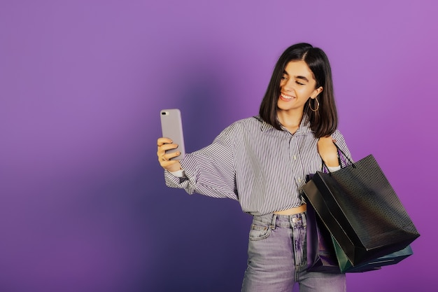 Улыбающаяся девушка в повседневной одежде держит пакеты с покупками после покупок и делает селфи на телефоне, изолированном на фиолетовой поверхности