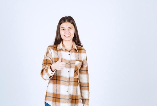Улыбающаяся девушка в клетчатой рубашке показывает палец вверх.