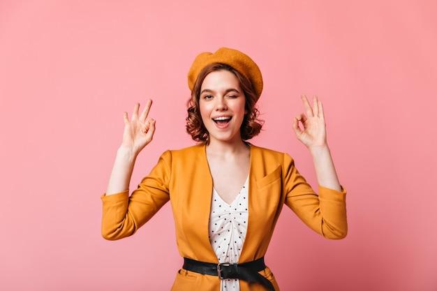 カメラでウインクするフランスのベレー帽の笑顔の女の子。ピンクの背景に大丈夫な兆候を示すスタイリッシュな若い女性の正面図。