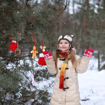 冬の森の中で細工されたおもちゃで松の木を飾る面白い帽子と暖かいコートの笑顔の女の子