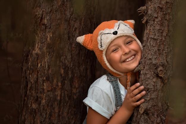 숲에서 여우의 재미 있는 모자 의상에서 웃는 소녀