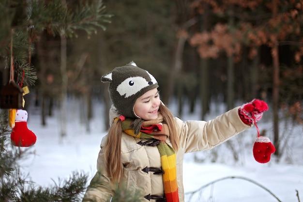 冬の森の中で細工されたおもちゃで松の木を飾る面白い帽子の笑顔の女の子