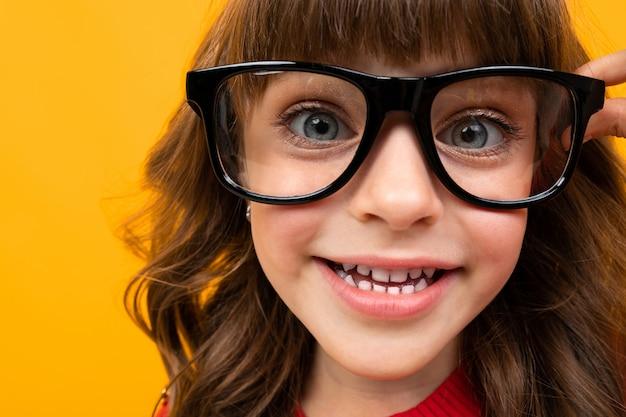 Улыбающаяся девушка в очках крупным планом на апельсине