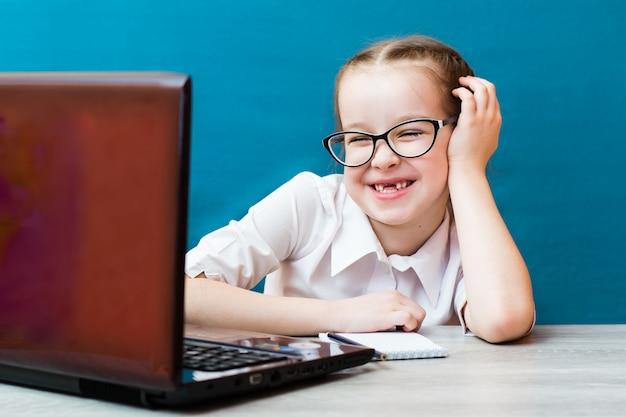 Улыбающаяся девушка в очках работает за ноутбуком за столом