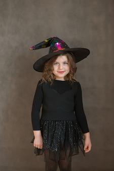 Улыбающаяся девушка в костюме ведьмы хэллоуина на сером фоне