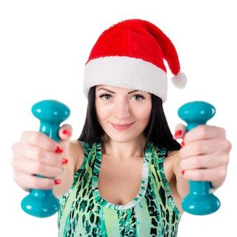 Улыбающаяся девушка в шляпе санта-клауса, делать упражнения с гантелями.