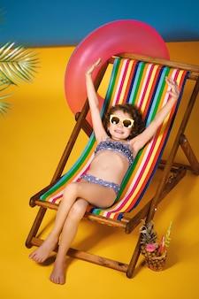 ライラック水着とサングラスをかけた笑顔の女の子が、足を組んで日光浴をしているレインボーデッキチェアに横たわっています。