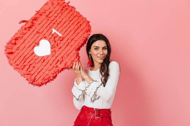 Улыбающаяся девушка в длинных красных серьгах и кожаной юбке с улыбкой демонстрирует лайк из instagram.