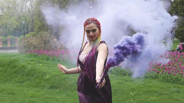 Улыбающаяся девушка в фиолетовом атласном платье с длинными разноцветными косами и эффектным блестящим макияжем. дым фиолетового цвета накрывает девушку в весеннем парке