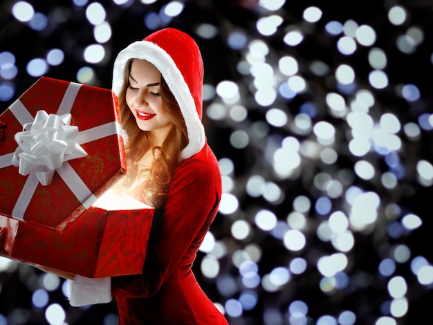 Улыбается девушка в красном костюме, открывая подарок на новый год 2019 года.