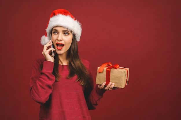 Улыбающаяся девочка в одежде санта с рождественскими подарками, звоня по телефону.