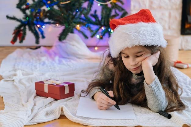 산타 클로스에 게 선물에 대 한 편지를 쓰고 산타 모자에 웃는 소녀.