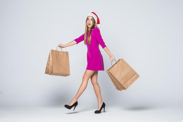 Улыбающаяся девушка в коротком розовом платье и новогодней шапке на каблуках держит бумажные пакеты, изолированные на белом фоне