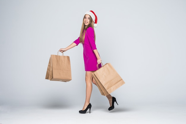 Улыбающаяся девушка в коротком розовом платье и новогодней шапке на каблуках держит бумажные хозяйственные сумки, изолированные на белом фоне