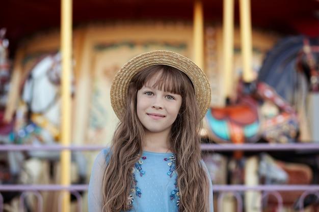 Улыбающаяся девушка в соломенной шляпе возле карусели на ярмарке портрет милой девушки в парке развлечений