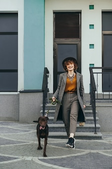 Улыбающаяся девушка в стильной одежде и шляпе на прогулке по улице