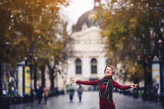 秋のセーターの笑顔の女の子が通りに立って、横に腕を広げてライフスタイル