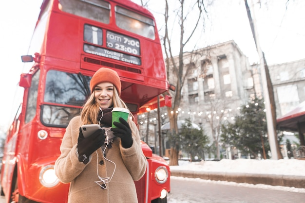 따뜻한 옷을 입고 웃는 소녀는 손에 커피와 스마트 폰 한 잔과 함께 겨울 날 거리에 서