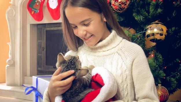 장식된 크리스마스 트리 옆에 귀여운 새끼 고양이를 들고 흰 스웨터를 입은 웃는 소녀