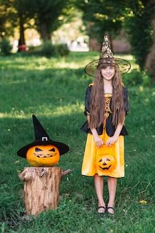 Улыбающаяся девушка в костюме ведьмы возле тыквы