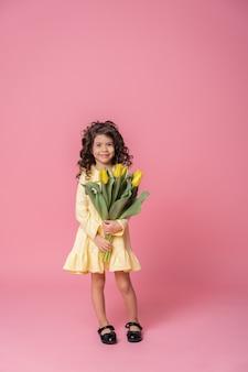 핑크 스튜디오 배경에 노란색 드레스에 웃는 소녀. 튤립 꽃 부케와 쾌활 한 행복 한 아이입니다.