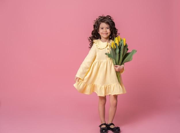 Улыбающаяся девушка в желтом платье на розовом фоне студии. веселый счастливый ребенок с букетом тюльпанов.