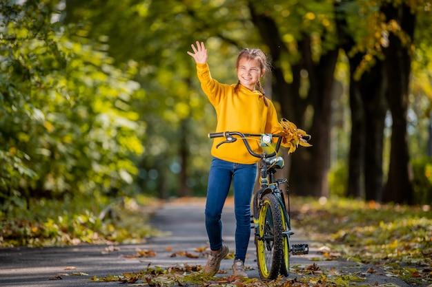 黄色いセーターを着た笑顔の女の子が晴れた日に秋の公園を自転車で歩き、優しい手を振る。