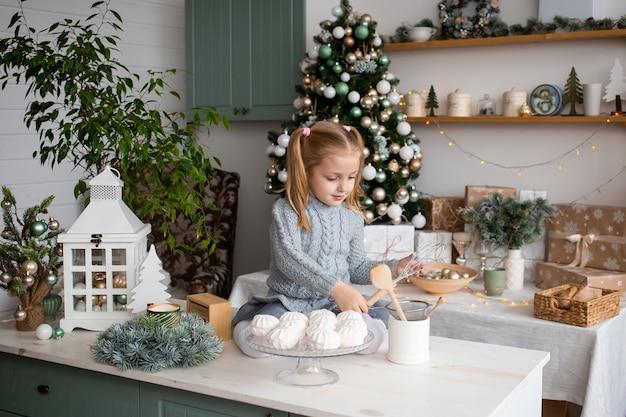 Улыбающаяся девушка играет сидя на кухонном столе.