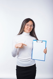 Smiling girl is pointing at a paper board over white.