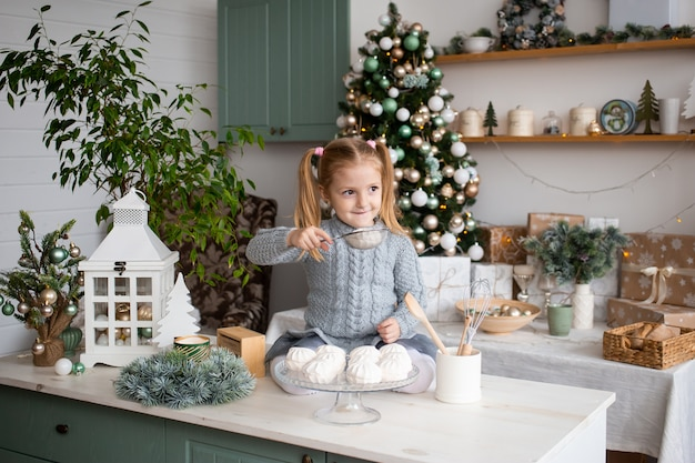 Smiling girl is sitting on kitchen table.