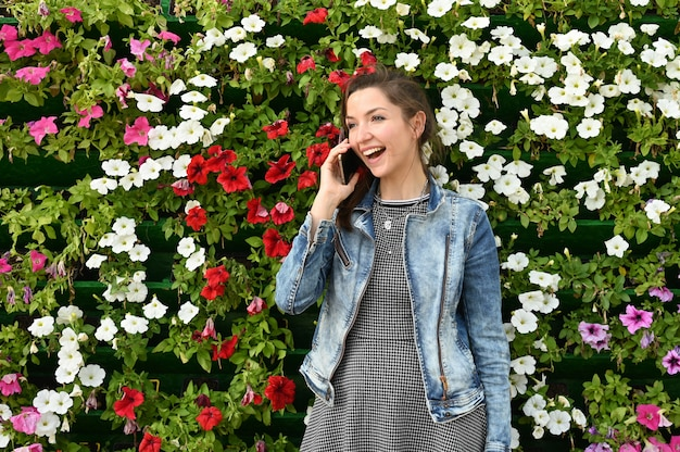 Smiling girl is talking on the space of flowers