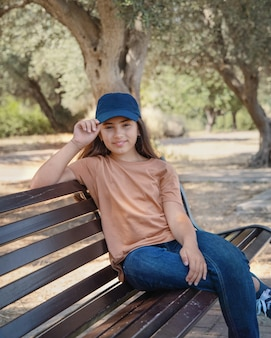 Smiling girl kid wearing t-shirt; jeans and baseball cap sits on the bench in the park