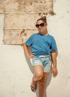 Tシャツ、ショートパンツ、サングラスを身に着けている笑顔の女の子の子供は、屋外の石の壁の近くに滞在し、カメラをまっすぐに見ています。 tシャツのモックアップ