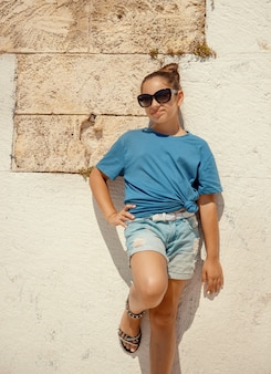 Smiling girl kid wearing t-shirt, shorts and sunglasses staying near a stone wall outdoor and looking stright into the camera. t-shirt mockup