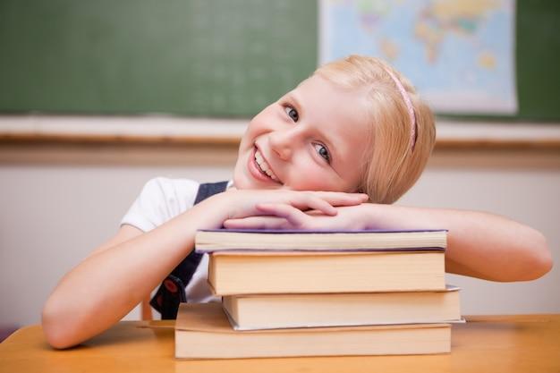 書籍に傾いている笑顔の女の子