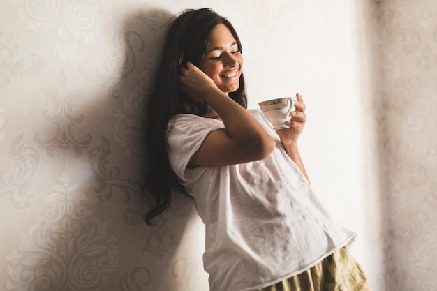 Smiling girl leaning on wallpaper holding coffee cup in hand