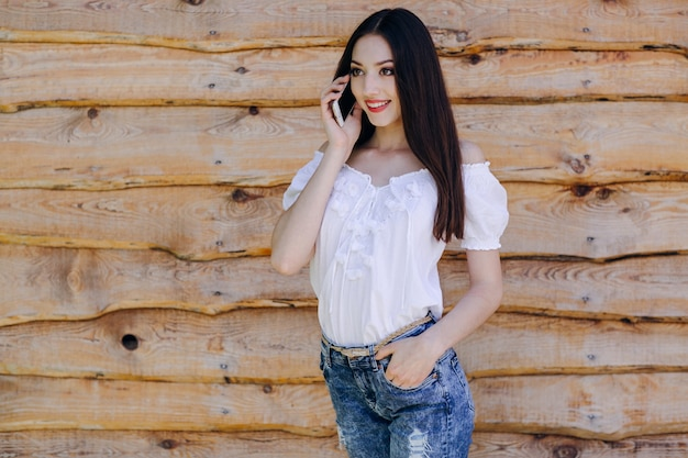 Smiling girl leaning on a wooden wall talking on the phone
