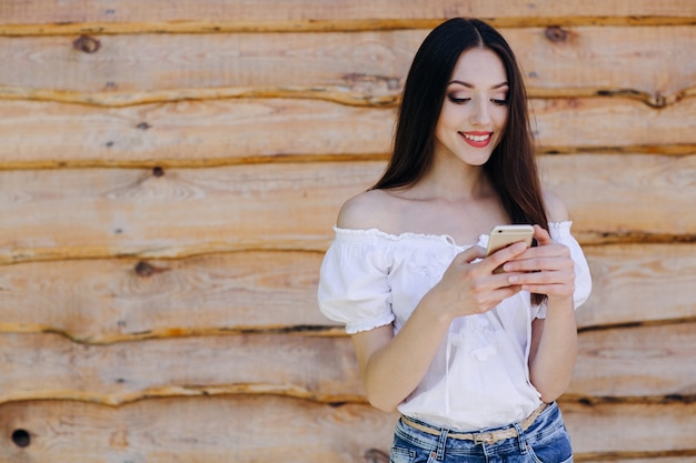 Smiling girl leaning on a wooden wall typing on her mobile phone