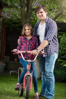 公園で父親と一緒に自転車に乗る方法を学ぶ笑顔の女の子