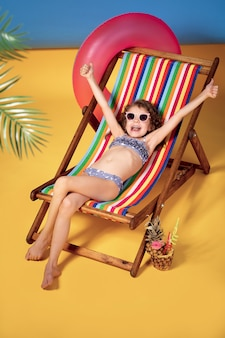 Smiling girl in lilac swimsuit and sunglasses lying in rainbow deck chair with crossed legs and sunbathing. raised hands up and smile.