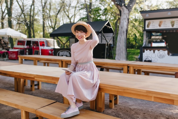 Smiling girl in long dress and trendy shoes sitting on wooden table holding mobile phone in hand