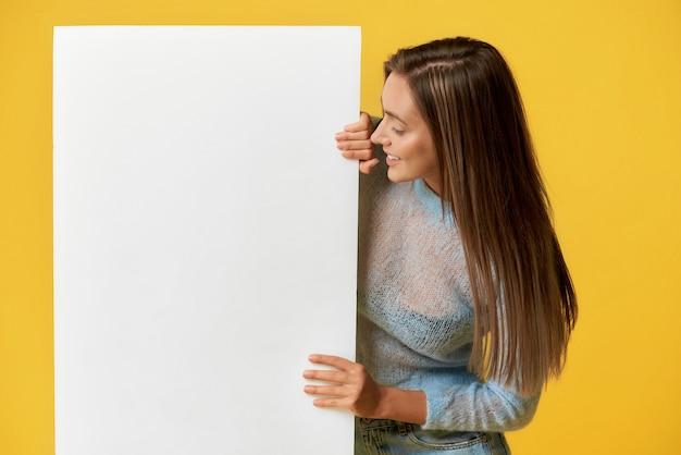 흰색 포스터를 보고 웃는 소녀