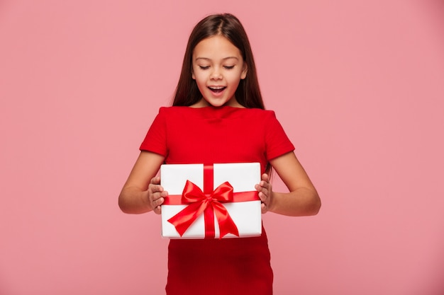Smiling girl looking at gift in hands and smiling isolated