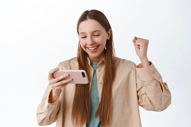 笑顔の女の子がスマートフォンを見て喜ぶ、ガッツポーズを喜ぶ、モバイルビデオゲームで勝つ、オンラインでの勝利を祝う、アプリで目標を達成する、白い壁の上に立つ