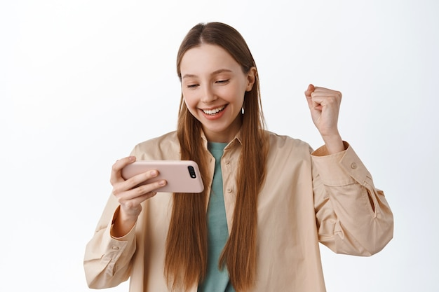 Smiling girl looks at smartphone and rejoice, fist pump pleased, winning on mobile video game, celebrating online victory, achieve goal in app, standing over white wall