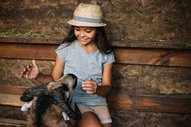 Smiling girl loving sheep in the barn