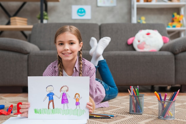 Smiling girl lying on carpet showing drawing of her family drawn on white paper